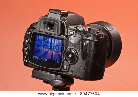 Digital camera on a tripod on an orange background view from the side of the monitor and viewfinder