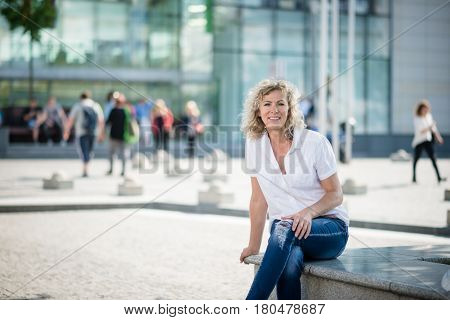 Mature woman with a lovely smile sitting in front of a building