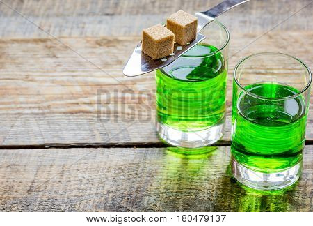 green absinthe in glass with sugar cubes on wooden table background mock up