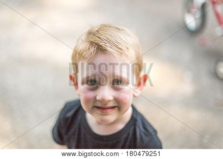 Young boy looking up at camera with a brave little smile.