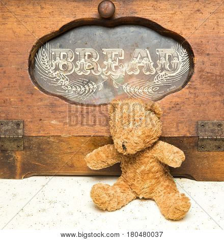 Brown Teddy Bear Sitting In Front Of An Old Bread Box