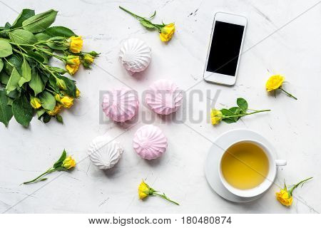 trendy office desk of woman with yellow roses and marsh-mallow on light marble background top view