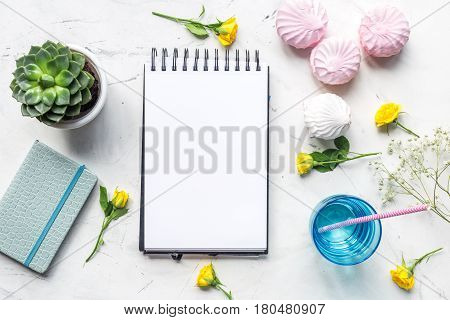 trendy office desk of woman with copybook, yellow roses and marsh-mallow on light marble background top view space for text