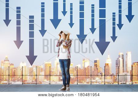 Young woman covering head with book while standing on concrete rooftop with railing city view and downward arrows. Failure concept