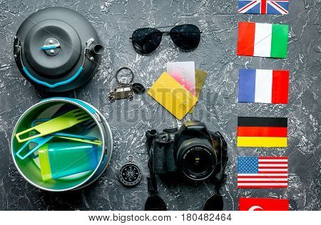 Outfit for trip with photo camera and sunglasses on gray table background top view