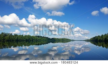 Reflection of white clouds in the blue water of the Daugava.