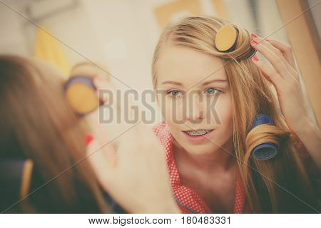 Woman Curling Her Hair Using Rollers
