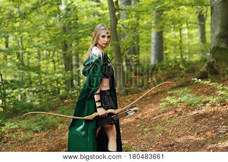 Beautiful young female elf looking to the camera over her shoulder while wandering at the woods with a bow in her hand fantasy hero character fairytale magic cosplay costume bravery courage legend.