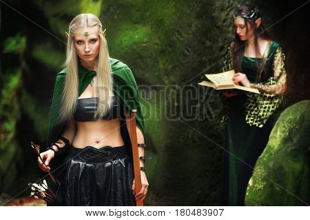 Shot of a gorgeous fearless female elf wearing a green cape holding a bow her female friend elf reading an old book on the background copyspace sisters friends mythical magical forest nature warrior.