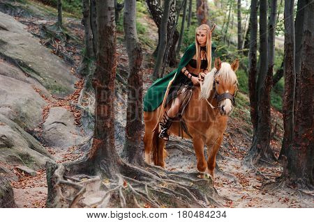 Young beautiful female elf sitting on a horse in the woods looking around copyspace cautious careful brave courage heroine superhero creature athletic activity nature calm balance film scene .