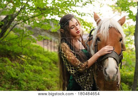 Beautiful young female elf with long dark wavy hair petting her horse resting in the woods forest nymph stroking her horse care pet love animals harmony caring owner gentle creature myth legend movie.