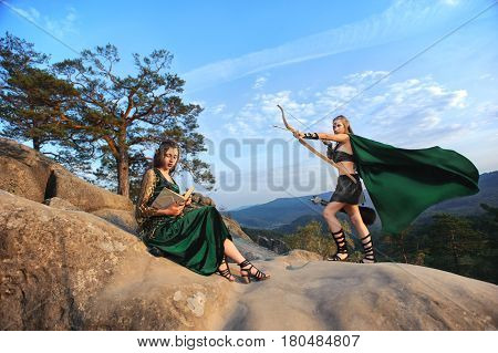 Shot of two beautiful fairy tale creatures female elves on top of a rock beautiful nature scenery on the background skies sky myth legend cosplay princess warrior femininity courage bravery fantasy.