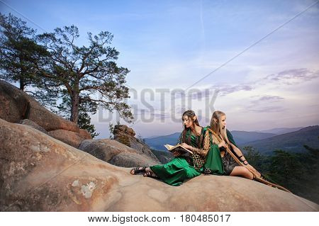 Two beautiful female elves sitting on top of a mountain surrounded by woods copyspace skies rest resting fairytale costume movie fantasy hero legendary mythology creatures nature mystery elf.