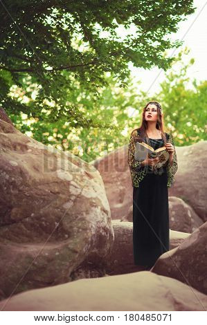 Vertical shot of a gorgeous young brunette female elf standing on a rock at the forest with an old book in her hands copyspace nature fantasy costume masquerade sensuality femininity fairytale myth.