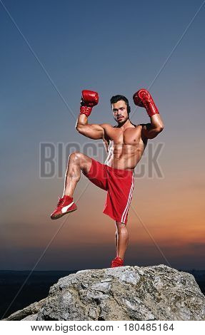 Vertical full length shot of a strong muscular male boxer posing outdoors on sunset wearing boxing gloves champion power strength fighter masculinity sports motivation competitive concept.