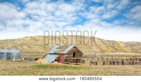 A leaning brown wooden shed collapsing toward a pasture fence with grain bins in the background in a valley in front of rocky hills in Montana landscape