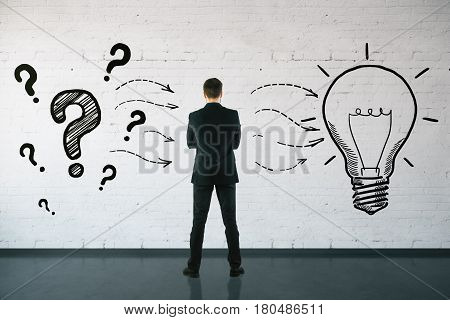 Back view of thoughtful businessman in brick interior with drawn questions and lamp. Idea concept. 3D Rendering