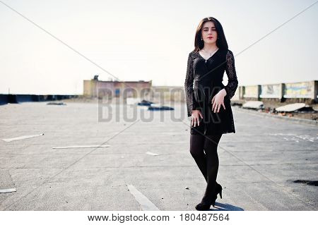 Portrait Brunette Girl With Red Lips Wearing A Black Dress, Tights And Shoes On Heels Posed On The R