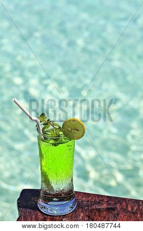 Glass of the green soft drink is on a beach table (Maldives The Indian Ocean)