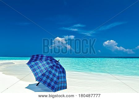 Blue umbrella is on a coral sandy beach Maldives The Indian Ocean