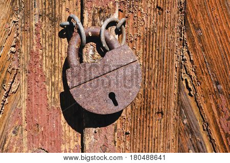 Old rusty lock on wooden doors with cracks close-up view