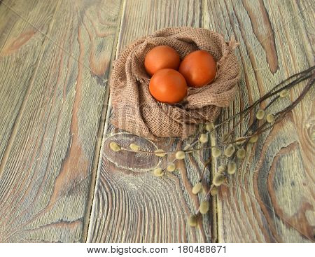 Easter color eggs and willow are a holiday symbol. Eggs and a willow are on a wooden table