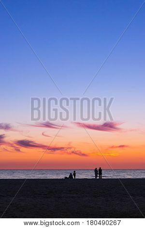 Warm summer night on sandy beach by sea. Sunset at Baltic sea in Lithuanian resort Palanga. Rays of sun shine through the low rare cirrus clouds. Lines of people on sandy beach