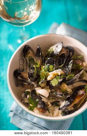 Mussels in sashes in sauce in a ceramic bowl vertical