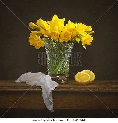 Bunch of spring daffodils with cut lemons still life on rustic table