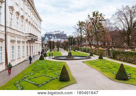 Salzburg, Austria - December 25, 2016: Green flowerbed garden and Hohensalzburg Festung in Salzburg, Austria