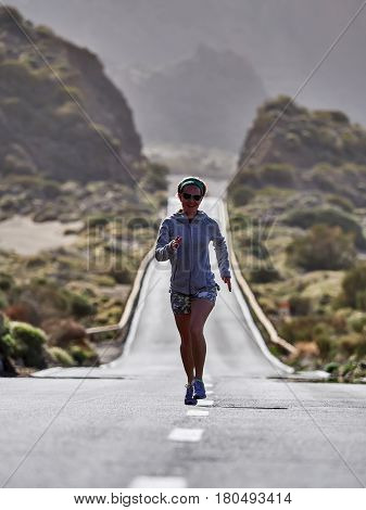 young Female Traveler running on the road in Teide volcano crater, Tenerife, Spain