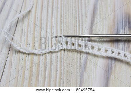 White crochet organic cotton chain pattern and steel hook on wooden background. Irish crochet lace craft bridal style