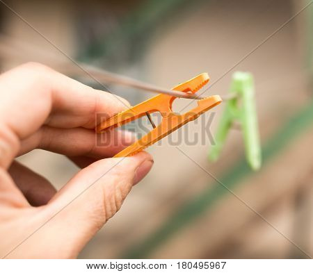 Clothespin in a hand on a clothesline .