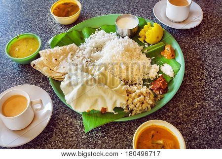 Hot coffee and plate with South Indian food thali with rice and spicy vegetables on palm leaf in indian cafe. Asian food still-life.