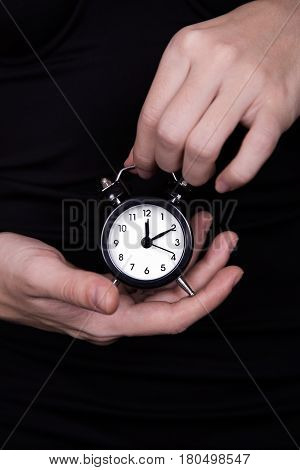 Female hands holding black and white little clock on dark background. Concept of time and style.