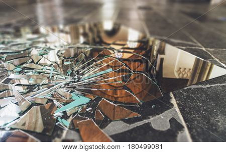 Close-up shards of broken mirror on stone floor inside building hall