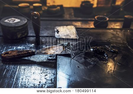 Black mastic spread over surface with putty knife in vintage artists workshop