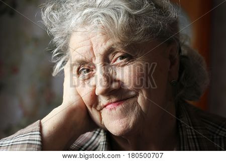 Elderly woman face on a dark background