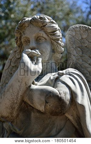 SAINT MARYS, GA - APR 28, 2012 A statue of an angel with her hand to her mouth overlooks graves at Oak Grove Cemetery.