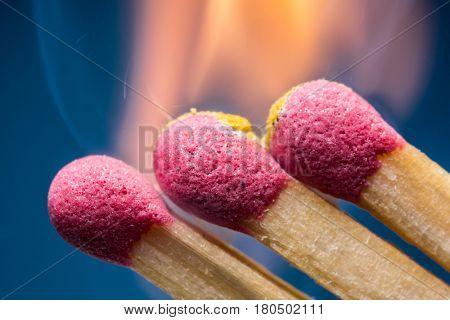 Burning safety matches. Blue background.