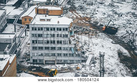 View from high point of dismantling and demolition of a multi-storey house in residential district: construction machinery piles of garbage powdered with snow heavy machinery around winter cloudy day