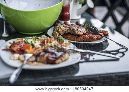Assorted delicious grilled meat with salad in background on white plate on table for family bbq party