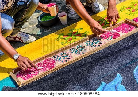 Antigua, Guatemala - March 26 2017: Locals spoon dyed sawdust through wooden stencil to decorate Lent carpet for procession in colonial town with most famous Holy Week celebrations in Latin America.