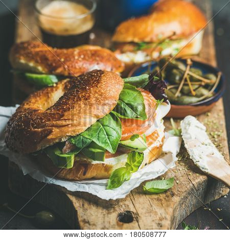 Breakfast with bagels with salmon, avocado, cream-cheese, basil, espresso coffee, capers on rustic wooden board over dark background, selective focus, square crop. Healthy or diet food concept