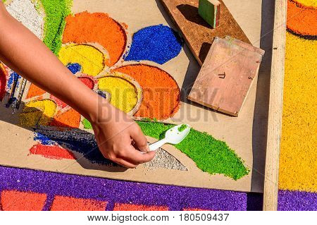 Antigua, Guatemala - March 26 2017: Local spoons dyed sawdust through stencil to decorate Lent carpet for procession in colonial town with most famous Holy Week celebrations in Latin America.