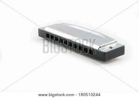 New Harmonica on a white background - metal.