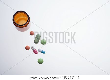 various medicine drugs with pill jar on lab light table photo top view flat lay