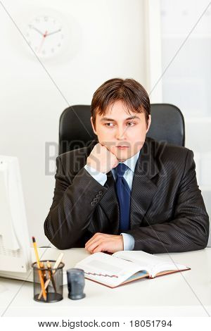 Pensive businessman sitting at office desk and keep head on hand