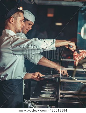 Food concept. Young handsome chefs in white uniform kindle coals and put raw marinated meat on the grill plate in interior of restaurant kitchen. Preparing traditional beef steak on barbecue oven.