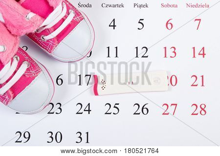 Pregnancy Test With Positive Result And Baby Shoes On Calendar With Polish Inscription, Expecting Fo